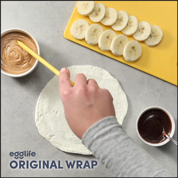 Hand dipping into peanut butter for a EggLife wrap with bananas and chocolate sauce.
