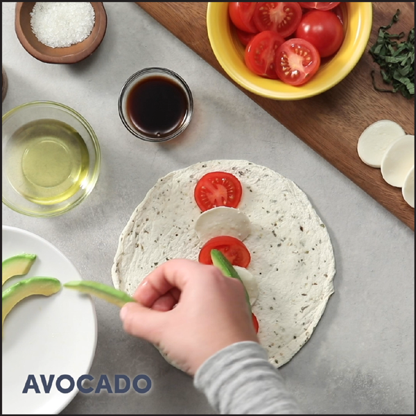 Hand placing avocado on a EggLife wrap with tomatoes and cheese.